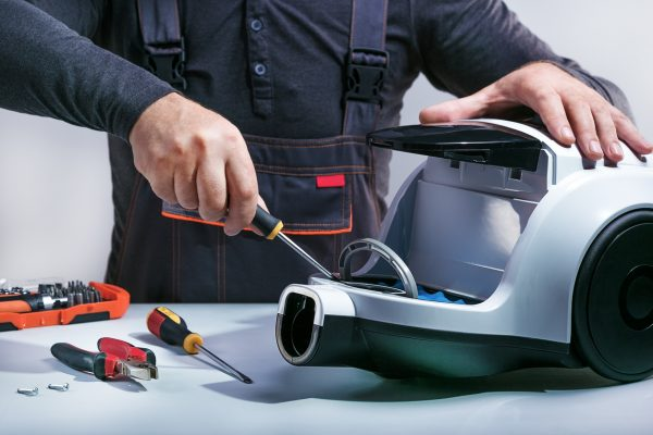 Repairman repairing of vacuum cleaner.