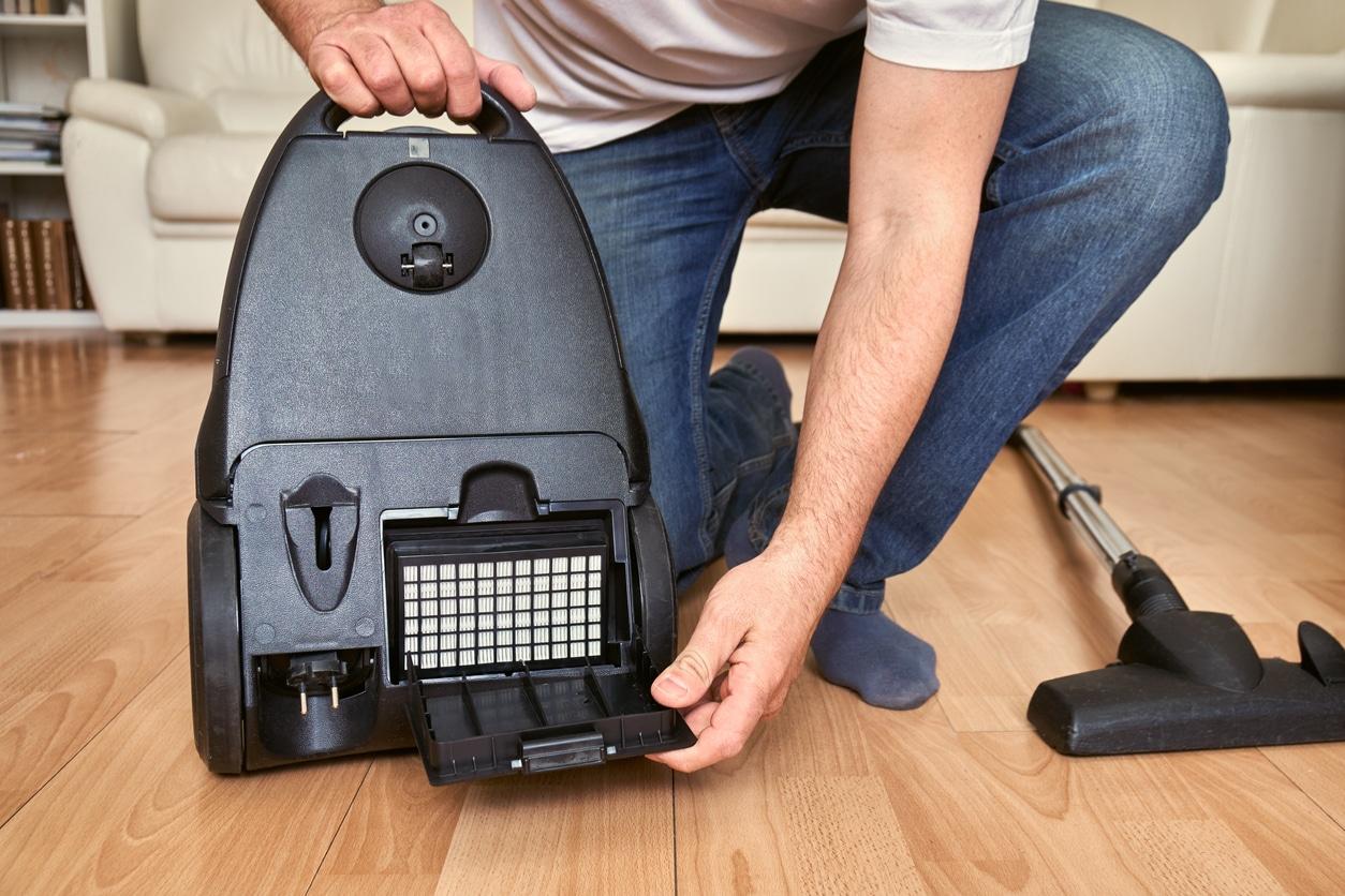 Man replacing an air filter in vacuum cleaner at home