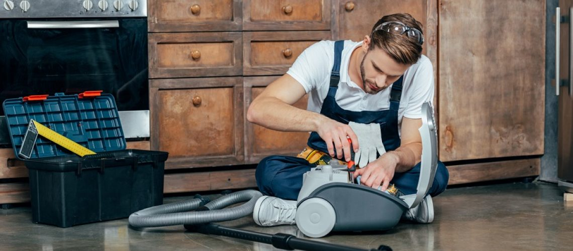 professional repairman fixing vacuum cleaner